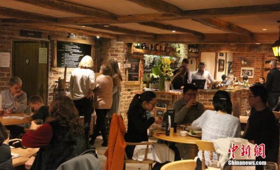 """位于伦敦郊外卡兹顿路边、名为""""卡兹顿之犁""""的酒吧,是一座两层楼的小酒吧。在拥有6万多酒吧、""""酒吧文化""""享誉世界的英国,显得极为平常,但因前首相卡梅伦经常光顾,""""首相酒吧""""之名不胫而走。图为不少华人、华侨和中国游客慕名远道而来。中新社记者 张平 摄"""