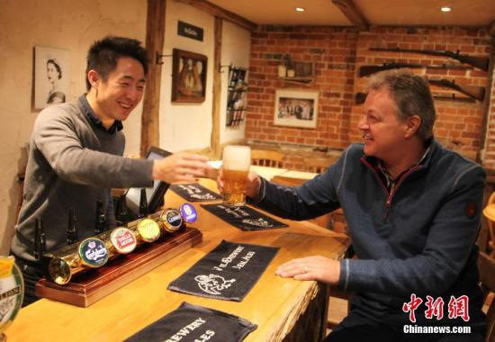 """位于伦敦郊外卡兹顿路边、名为""""卡兹顿之犁""""的酒吧,是一座两层楼的小酒吧。在拥有6万多酒吧、""""酒吧文化""""享誉世界的英国,显得极为平常,但因前首相卡梅伦经常光顾,""""首相酒吧""""之名不胫而走。图为获得该酒吧经营权的张羽(左)与酒吧原老板史蒂夫・霍林斯(Steve Hollings)在吧台前交流。中新社记者 张平 摄"""