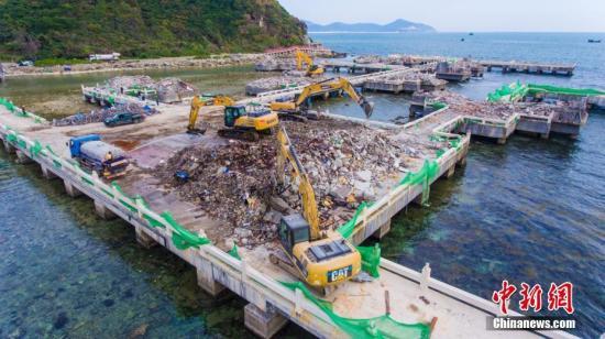 """1月17日,记者在备受社会各界关注的三亚半山半岛洲际度假酒店""""海上餐厅""""拆除现场看到,该""""海上餐厅""""平台以上17栋、4846.72平方米的主体建筑已全部拆除完毕,当地执法部门工作人员正在清理拆除后的建筑垃圾。当地政府将严格按照拆除方案争取6月底前将""""海上餐厅""""拆除完毕,达到恢复海域原状要求。据了解,该""""海上餐厅""""由一个能容纳百个餐位的主用餐区和15座由栈桥连通的独立贵宾包房组成。该项目建于三亚珊瑚礁国家级自然保护区内,于2011年5月完工并已投入使用,未获得海洋主管部门审批的海域使用权,未通过海洋主管部门的环评核准,属于未批先建项目。 骆云飞 摄"""