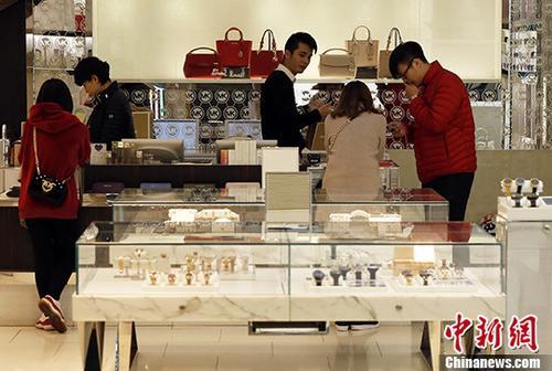 1月17日,顾客在上海某商场选购商品。当日,贝恩公司发布的《2017年中国奢侈品市场研究》报告显示,在经历了三年的减速期后,中国个人奢侈品消费在2016年第三季度迎来了反弹并在2017年强势增长。其中,中国消费者在内地市场的奢侈品消费增速超过了海外市场,内地市场增幅达到了20%。&#10;<a target='_blank' href='http://www-chinanews-com.meritocratedu.com/'>中新社</a>记者 汤彦俊 摄