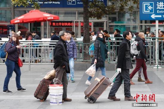 资料图:游客拖着行李准备进站。 殷立勤 摄