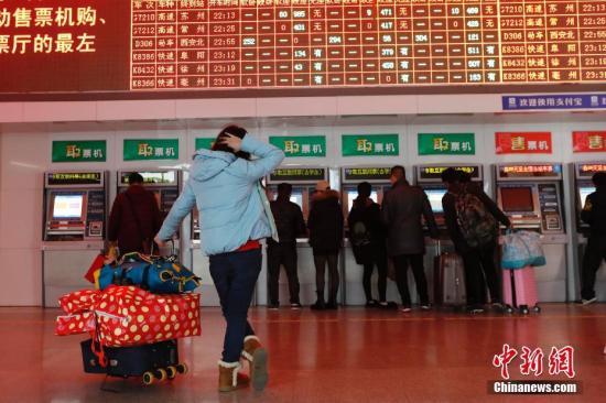 资料图:旅客在铁路上海站售票大厅内查看剩余车票信息。 殷立勤 摄