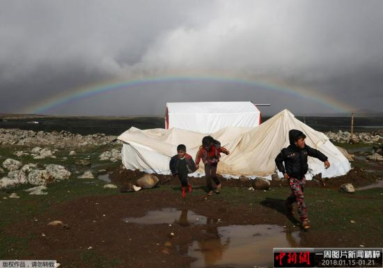 当地时间1月19日,叙利亚南部城市库奈特拉的一个难民营上空出现彩虹,孩子们在泥泞中奔跑玩耍。