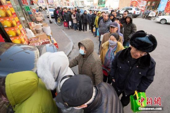 资料图:1月22日,山西太原,民众拎着大小各异的空壶排长队购买老陈醋,为春节做储备。中新社记者 武俊杰 摄