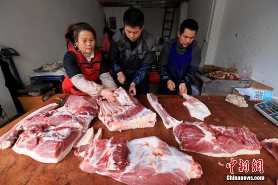 居民在家中切猪肉。谭凯兴 摄