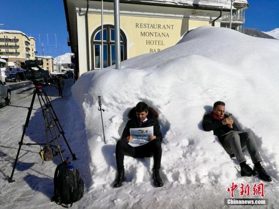 """当地时间1月23日,2018年世界经济论坛年会(""""冬季达沃斯"""")在瑞士小城达沃斯开幕。今年的冬季达沃斯年会开幕前夕,当地迎来了多年不遇的强降雪。图为两名记者当天坐在积雪上休息。/p中新社记者 彭大伟 摄"""