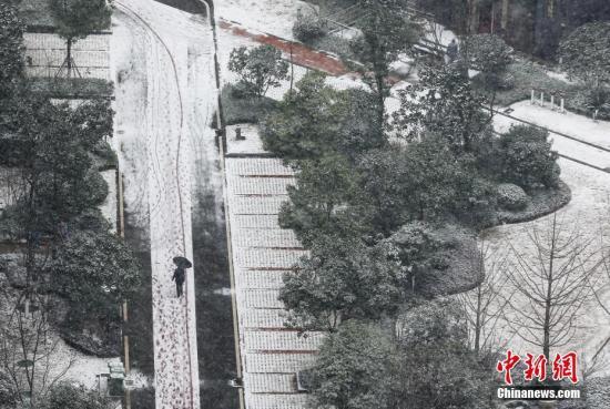 1月26日,武汉市民在大雪中出行。当日,武汉再次迎来雨雪天气,城市建筑被白雪覆盖。中新社记者 张畅 摄