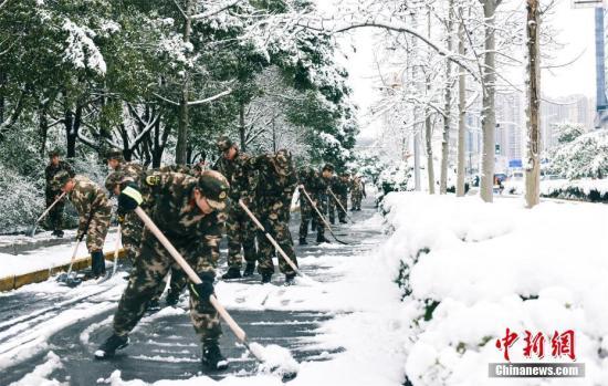资料图:浙江湖州消防官兵全力铲除积雪,确保市民出行安全。中新社记者 李欢 摄