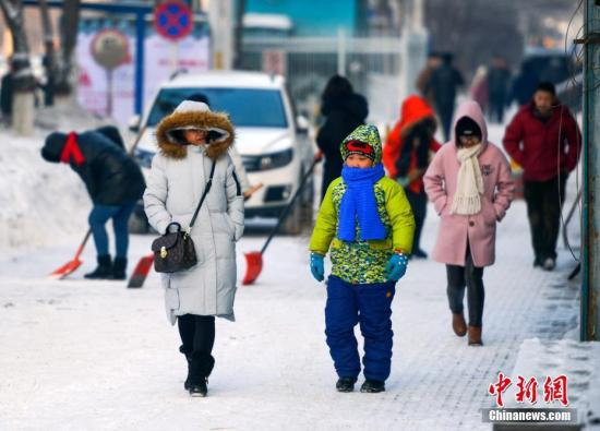 1月26日,新疆乌鲁木齐市街头,外出民众穿着厚厚的冬衣抵御寒冷。当天,该市最低气温达到零下26摄氏度。中新社记者 刘新 摄