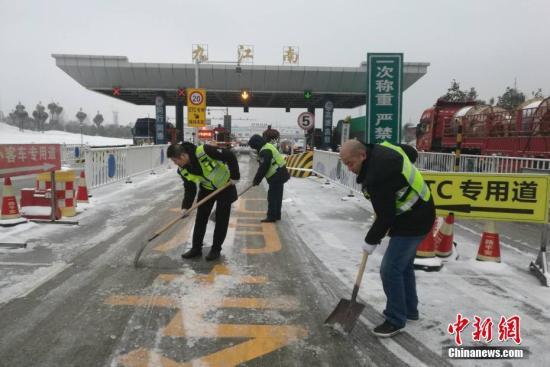 资料图:江西高速公路工作人员在收费站通道进行扫雪除冰作业。钟欣 摄
