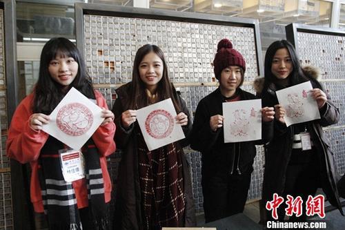 1月26日,来北京参加2018寒假台湾青年学生中华文化研习营的80余位台湾师生来到武英造办博物馆,体验传统造纸和印刷工艺。图为台生与自己制作的雕版印刷作品合影。中新社记者 陈小愿 摄