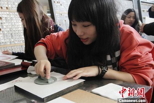1月26日,来北京参加2018寒假台湾青年学生中华文化研习营的80余位台湾师生来到武英造办博物馆,体验传统造纸和印刷工艺。图为台生体验雕版印刷。中新社记者 陈小愿 摄