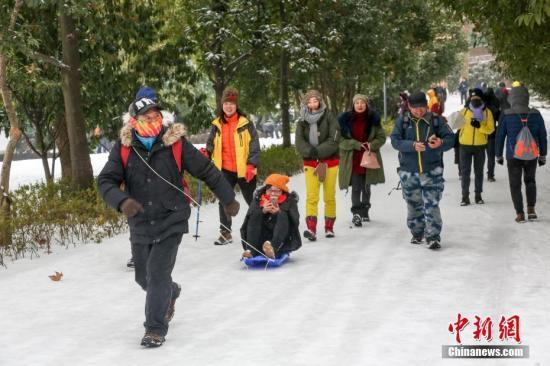 1月27日,武汉东湖,前来游园的市民和游客玩起人力雪橇。经历一夜大雪的武汉已是一片银装素裹。据气象部门预测,武汉市低温降雪冰冻天气将持续,未来两天最高气温在0℃以下,积雪冰冻有可能加重。中新社记者 张畅 摄