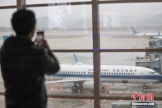 资料图:一名旅客正在拍摄客机。 中新社记者 瞿宏伦 摄