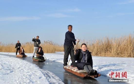 """资料图:民众坐""""冰床""""到白洋淀里游玩。中新社记者 韩冰 摄"""
