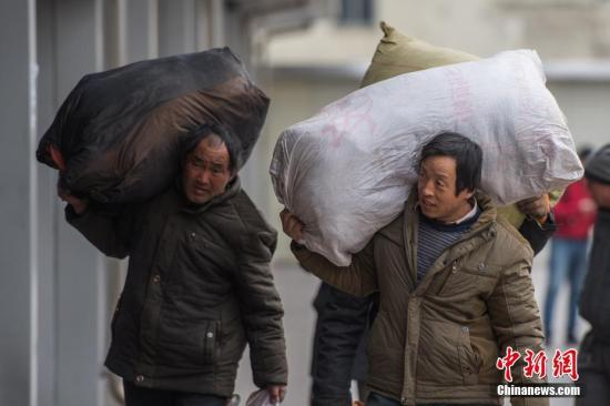 资料图:太原火车站中的农民工扛着大小行李。中新社记者 韦亮 摄