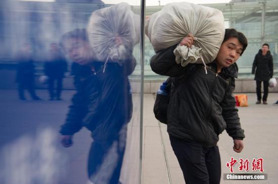 1月30日,山西太原火车站,农民工扛着大小行李返乡。(资料图)中新社记者 韦亮 摄