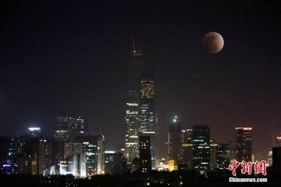 """罕见的月全食""""超级蓝血月全食""""亮相夜空,与北京CBD地区的灯光相映成趣。/p中新社记者 李慧思 摄"""