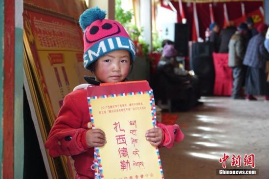 资料图:藏族小朋友手持春联。文/孙翔 曾嘉 图/孙翔