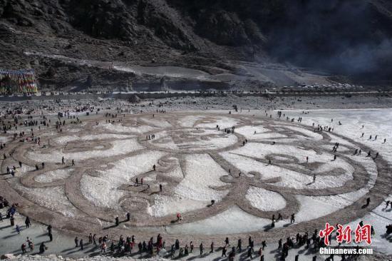 """2018年2月2日,在青海省玉树藏族自治州称多县海拔3600多米的通天河冰面上,当地藏族民众""""沙为墨冰为纸"""",""""绘""""写藏传佛教""""六字真言""""及""""吉祥八宝""""图案冰沙玛尼,以此祈福新的一年世界和平、五谷丰登、六畜兴旺。图为当地藏族民众制作的冰沙玛尼。中新社记者 罗云鹏 摄"""