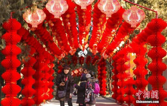 2月2日,北京地坛公园,市民经过挂满红灯笼的通道。随着农历春节的临近,北京城年味渐浓。<a target='_blank' href='http://www.torvenius.com/'>中新社</a>记者 侯宇 摄