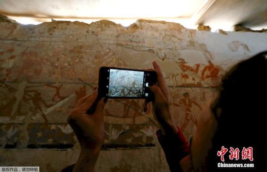 资料图:游客用手机拍下壁画。