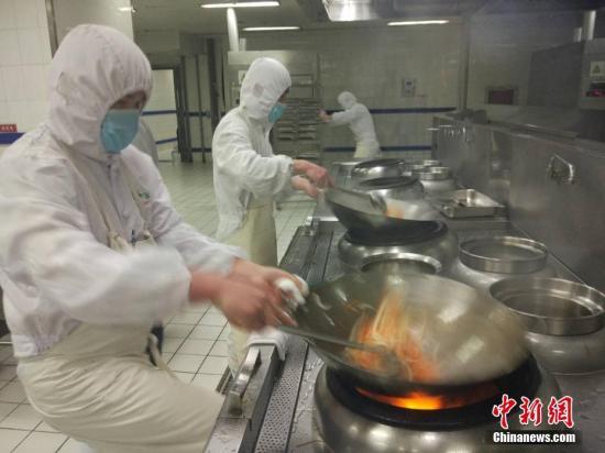 资料图:厨师在制作炒菜。