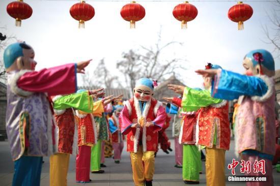 """资料图:2月8日,天津杨柳青镇,年画舞队在表演中,传统的大头娃娃""""走""""下了年画,舞出民俗之美。当天,第十五届西青区民俗文化旅游节正式拉开帷幕。中新社记者 佟郁 摄"""