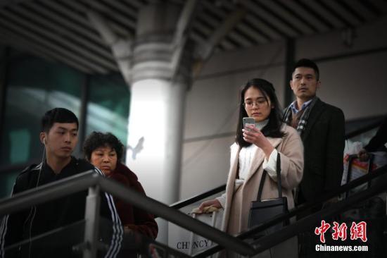资料图:走在楼梯上,人们也还是离不开手机。王东明 摄