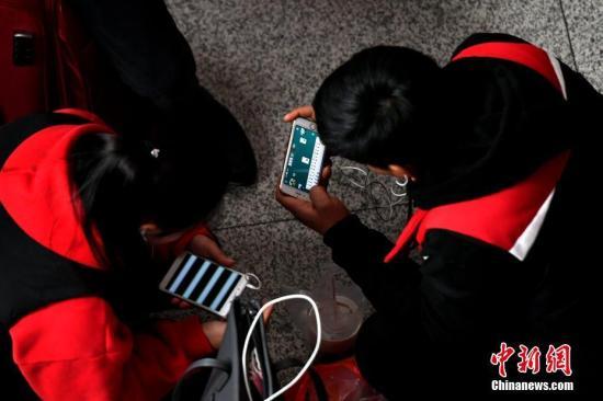 资料图:用户正在用手机打游戏。王东明 摄