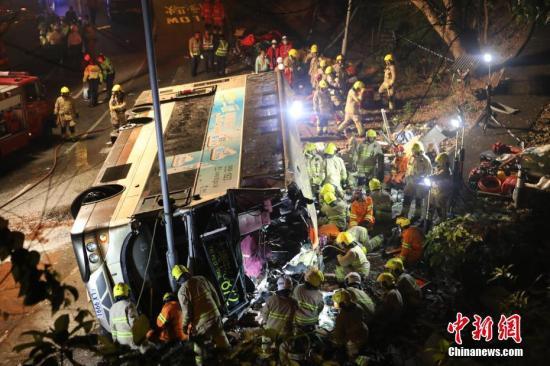 据香港媒体2月10日报道,一辆双层巴士当日在香港新界一条公路上失事侧翻,已造成19人死亡,数十人受伤。当日,一辆872路双层巴士在新界大埔公路行驶时侧翻。现场照片显示,巴士车身损毁严重,挡风玻璃破碎,地面疑有油污。据警方消息,17男2女在现场证实死亡,数十人受伤。/p中新社记者 麦尚旻 谢光磊 摄