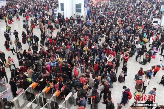 """2月11日,深圳北站迎来春运客流高峰,连续三日日客流发送量约在19.5万人次。深圳北站候车大厅内外人流如潮、有序候车乘车,铁路客运工作人员、公安、志愿者等全力保障春运铁路旅客出行,旅客踏上返乡路,离""""年""""更近了。 中新社记者 陈文 摄"""
