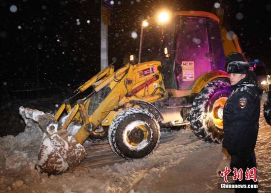 机上包括3名未成年人在内的65名乘客和6名机组人员全部遇难。一名警察在客机坠落地点外围指挥铲车清雪。<a target='_blank' href='http://www.chinanews.com/'>中新社</a>记者 王修君 摄