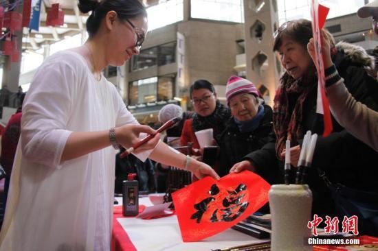 当地时间2月11日,加拿大第二大城市蒙特利尔举行欢乐春节庙会。图为女书法家在现场为华社民众题写挥春。这是蒙城连续第二年在农历新年前夕由华人社区联合举办欢乐春节庙会。参与筹办庙会的侨团由第一届的70多个增至本届的近百个。<a target='_blank' href='http://www.chinanews.com/'>中新社</a>记者 余瑞冬 摄