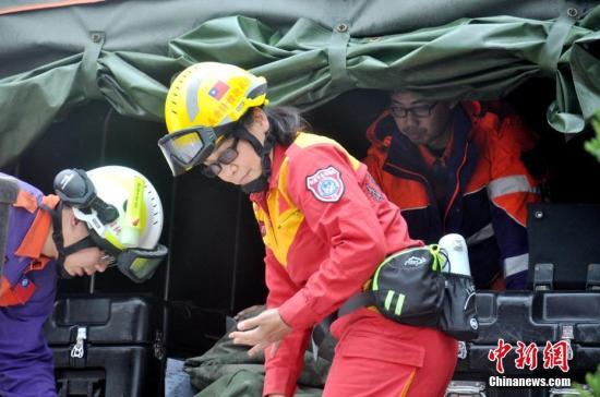 """台湾花莲地震最后两名失联人员2月11日上午被证实罹难。图为11日从地震""""重灾区""""花莲云门翠堤大楼撤离的救援人员。 <a target='_blank' href='http://reggaechina.com/'>中新社</a>记者 肖开霖 摄"""