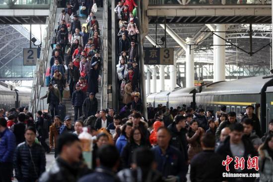 资料图:2月13日,大批旅客在南京火车站乘坐火车出行。 中新社记者 泱波 摄