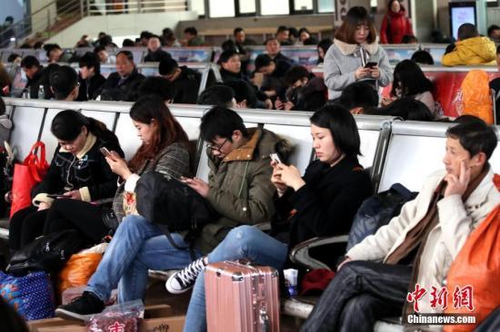 资料图:2月14日,河南郑州火车站,旅客在候车室里拿着手机打发时间。 <a target='_blank' href='http://www.chinanews.com/'>中新社</a>记者 王中举 摄