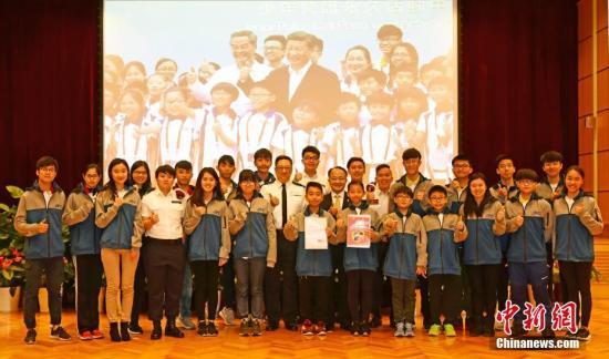 """资料图:2018年2月15日,中央政府驻港联络办公室主任王志民邀请郭宏��、罗颢凝同学等26位香港""""少年警讯""""成员来到中联办大楼,向他们转交了习近平主席的回信,转达了习主席对香港青少年的关心和问候。<a target='_blank' href='http://www.chinanews.com/'>中新社</a>记者 徐冬冬 摄"""