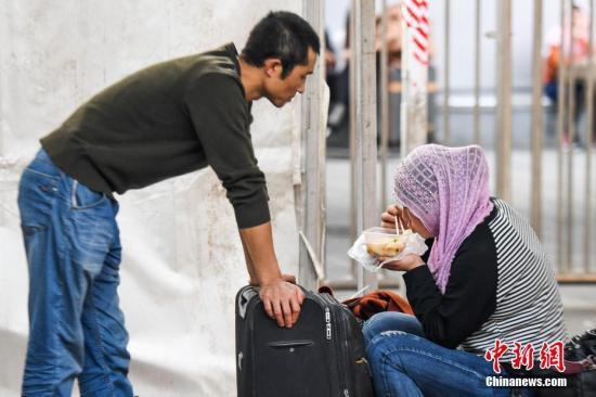 """2月15日傍晚,候车的旅客在广州火车站用餐。当日是农历大年三十,在万千家庭团聚吃年夜饭的时刻,不少旅客还在归途之中,只能在火车站吃一顿简单的""""年夜饭""""。<a target='_blank' href='http://www.chinanews.com/'>中新社</a>记者 廖树培 摄"""