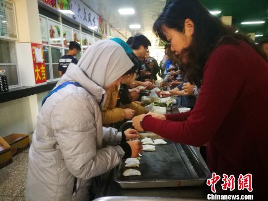 资料图:留学生在中国老师指导下包饺子。 王媛 摄