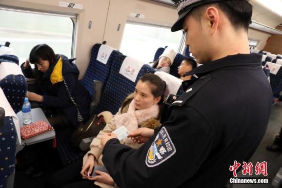 孔令扬在车厢内检查旅客的身份证件。胡宏 摄
