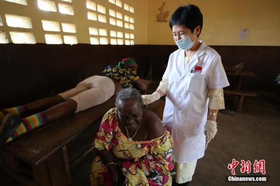 """从1963年中国派出第一支援外医疗队到今天,一批批来自中国各地奔赴世界各国进行医疗援助。新春将至,远在喀麦隆坚守的""""身着白大褂的外交官""""向中国亲人拜年。2018年2月15日,山西援非医疗队员向记者传回当地欢度春节的照片,并向记者讲述了在当地的工作、生活情况。图为第18批援喀麦隆医疗队中医大夫丰小鹏在喀麦隆巴扶桑地区为当地百姓做针灸治疗。受访者供图"""