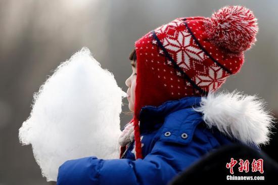 资料图:农历正月初二,北京一名儿童在吃棉花糖。中新社记者 富田 摄
