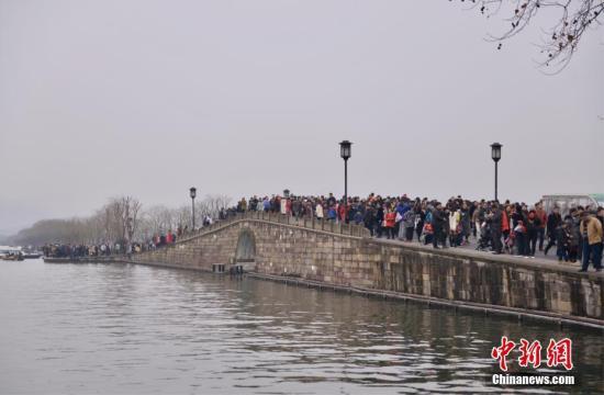 资料图:杭州西湖景区内的断桥上游人如织。中新社记者 李晨韵 摄