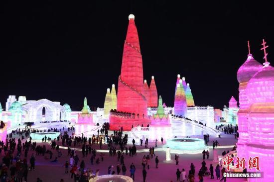 """2月19日,哈尔滨冰雪大世界景区游客众多,迎来春节旅游高峰。第十九届冰雪大世界将中国共建""""百花园""""主张与冰雪艺术相融,以冰雪还原""""一带一路""""沿线的经典景观与人文风采,建设各国游客共享的""""冰雪百花园""""。园区内,可以乘坐""""冰雪专列""""畅游莫斯科红场、哈萨克小镇,到曼谷打大象冰滑梯,甚至抵达""""南北极"""",在全球""""穿越之旅""""中感受冰雪魅力。图为游人在冰雪大世界园区内尽情享受着冰雪的乐趣。中新社记者 于琨 摄"""
