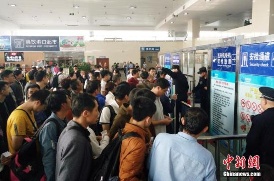 2月20日,海南海口新海港附近,大量旅客等待检票上船。中新社记者 尹海明 摄