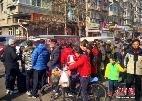 2月21日,天津民众排队品尝红姐煎饼�子。《舌尖上的中国3》播出之后,片中所拍摄的天津煎饼�子受到热捧。 中新社记者 佟郁 摄