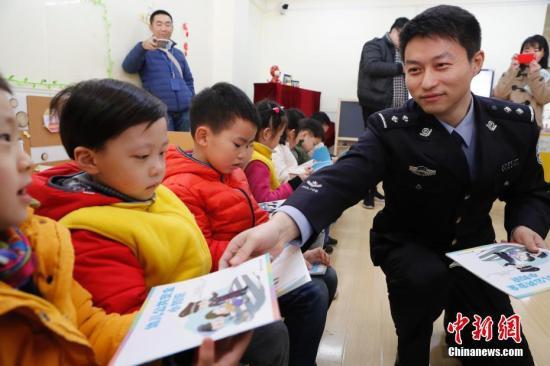 2月23日,上海市中小学开学第一天,一套全新的公共安全教育教学补充读本被发放到了全市中小学和幼儿园。图为上海市公安局法制总队一支队支队长沈雁辉向幼儿园孩子发放公共安全教育教学补充读本。 <a target='_blank' href='http://www.chinanews.com/'>中新社</a>记者 殷立勤 摄