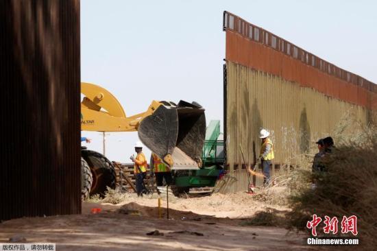 """资料图:当地时间2018年2月22日,美国加州卡莱克西科附近,美国海关和边境保护局对当地一段边境隔离墙进行更换。这标志着美国联邦政府启动了美国与墨西哥边境隔离墙的修建工程。此次工程覆盖范围约3.62公里,将由约9米高的新建墙体代替始建于上世纪90年代的旧墙体。美国海关和边境保护局称,该工程将有利于边境保护及增强公众和该局人员的安全。这是去年在加利福尼亚州圣迭戈附近修建8堵边境隔离墙""""样板墙""""后,特朗普政府批准的首个美墨边境隔离墙工程合同。美国内布拉斯加州一家建筑公司赢得了这份总额为1800万美元的隔离墙替换工程合同。 文字来源:人民网"""