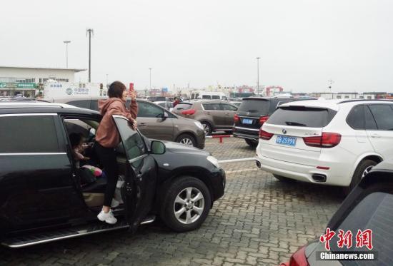 2月23日,海南海口新海港内,一位旅客拿出手机拍摄大批待渡车辆。受琼州海峡大雾影响,从19日开始的逾万车辆、旅客滞留海口现象23日还在持续。中新社记者 尹海明 摄
